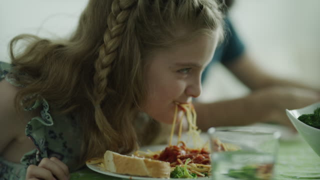 vidéos et rushes de close up of playful messy girl eating mouthful of spaghetti / lehi, utah, united states - espièglerie