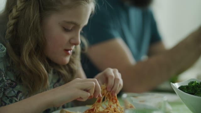 vídeos de stock, filmes e b-roll de close up of playful messy girl eating spaghetti with hands / lehi, utah, united states - espaguete