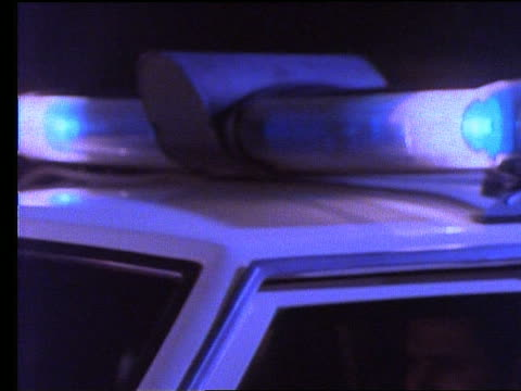 close up of police car flashing lights / people run by