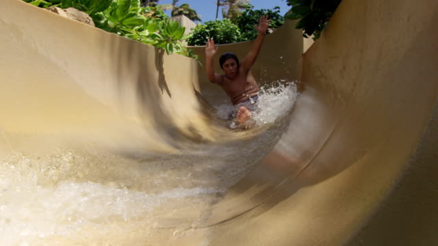 Close up of pool slide as boy comes sliding down