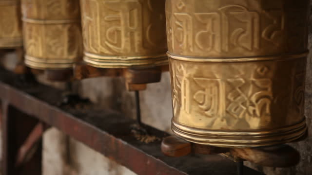 close up of prayer wheels turning in temple in tibet - traditionally tibetan stock videos & royalty-free footage
