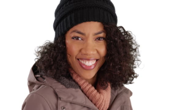 close up of pretty black female in cozy hat and coat smiling at camera in studio - warm clothing stock videos & royalty-free footage