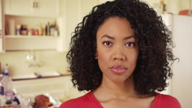 close up of pretty black female looking at camera thoughtfully inside kitchen - serious stock videos & royalty-free footage