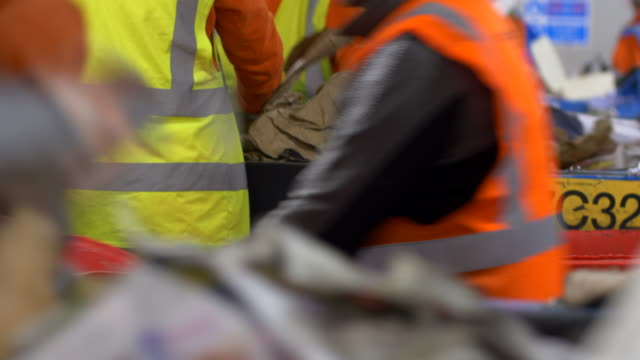 close up of recycling plant workers sort through waste plastics refuse and garbage on conveyor belts - manufacturing machinery stock videos & royalty-free footage