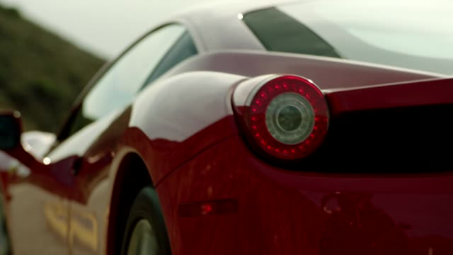 vídeos y material grabado en eventos de stock de close up of red ferrari driving up malibu canyon - luz trasera