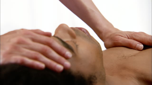 vídeos de stock e filmes b-roll de close up of reiki practioner placing hands on man's chest and forehead - reiki