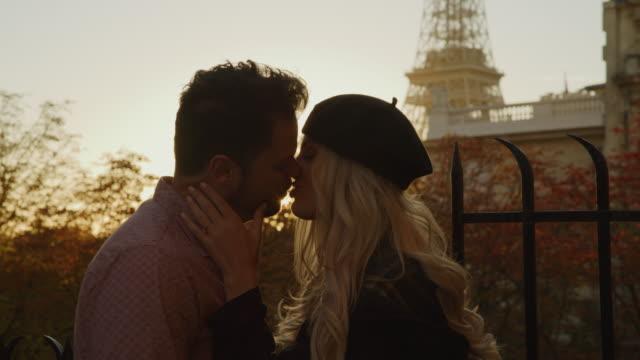 close up of romantic couple kissing at sunset near eiffel tower / paris, ile de france, france - baciare video stock e b–roll
