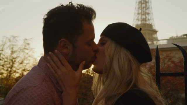 vídeos de stock, filmes e b-roll de close up of romantic couple kissing at sunset near eiffel tower / paris, ile de france, france - casal jovem