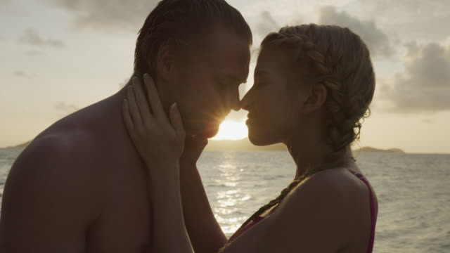 close up of romantic couple kissing near ocean at sunset / jamesby island, tobago cays, st. vincent and the grenadines - 上半身裸点の映像素材/bロール