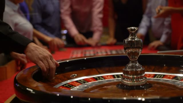 close up of roulette spinning while people are placing bets at the background - roulette stock videos and b-roll footage