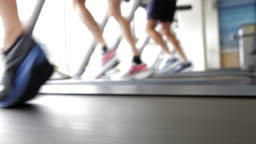 Close Up Of Runners Feet On Running Machine In Gym
