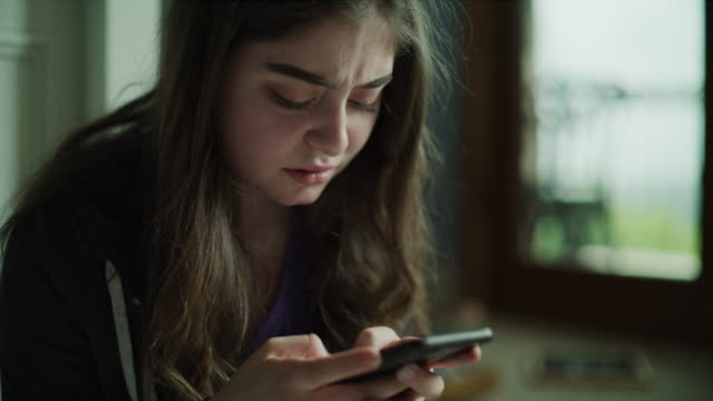 close up of sad girl texting on cell phone / cedar hills, utah, united states - tristezza video stock e b–roll