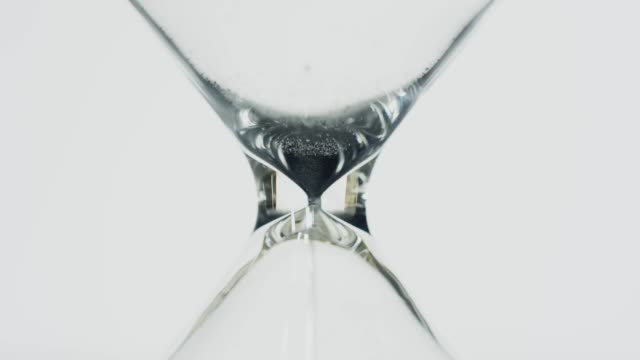 Close up of sand falling through hourglass
