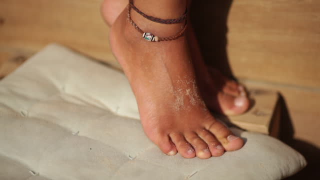Close up of sandy, tan, female feet with anklet at a beach cafe.