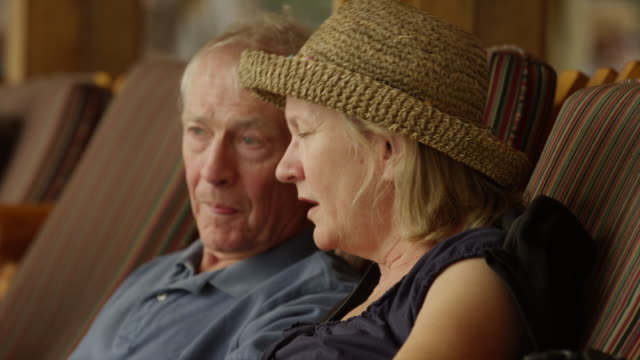 Close up of senior couple talking on lounge chairs / Idaho, United States