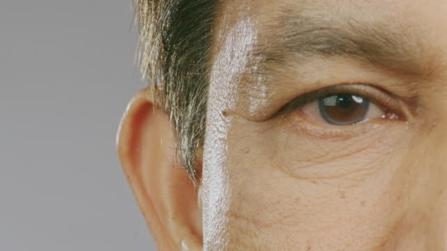 close up of senior man eye, open right eyes and moving around. asian man, macro shot. copy space. - blinking stock videos & royalty-free footage