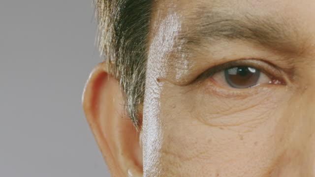先輩の目を閉じ、右目を開いて動き回る。アジアの男、マクロショット。スペースをコピーします。 - 瞬き点の映像素材/bロール