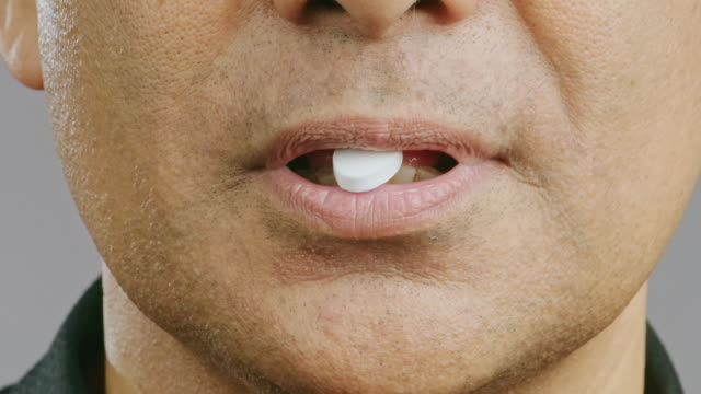 close up of senior man mouth, taking candy out of the mouth, happy smile. asian man, macro shot. - nutritional supplement stock videos & royalty-free footage