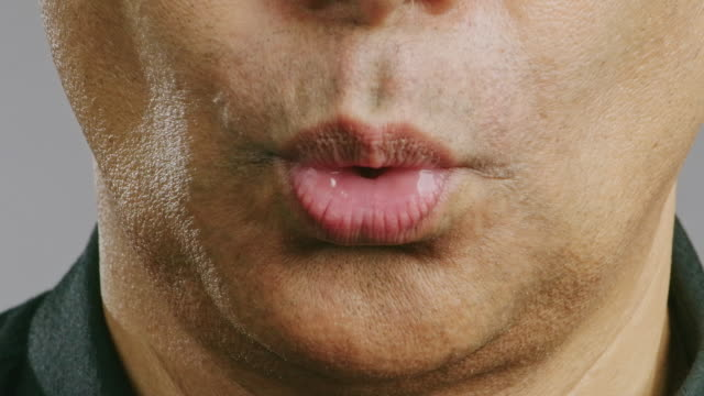 close up of senior man mouth, whistle. asian man, blow mouth whistle. - fischietto video stock e b–roll