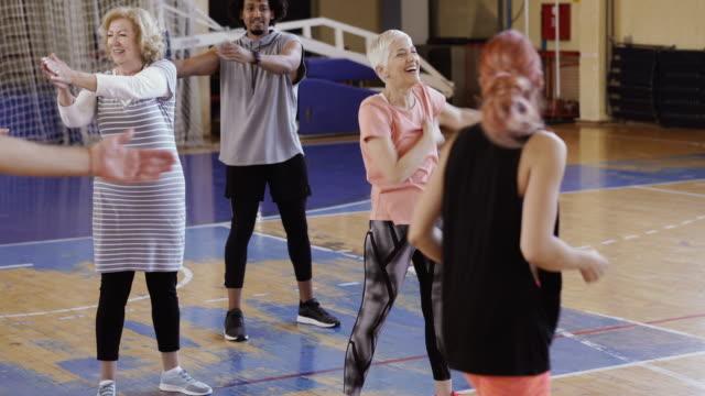 vídeos de stock, filmes e b-roll de feche acima dos braços de esticão sênior após a classe da dança - aula de exercícios