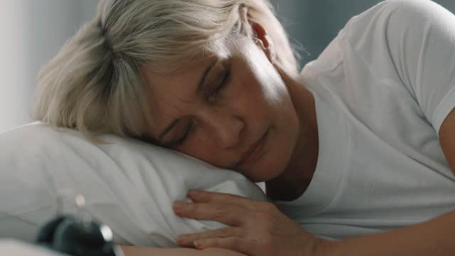 stockvideo's en b-roll-footage met sluit omhoog van hogere vrouw die moeite met slapen heeft. - een dutje doen