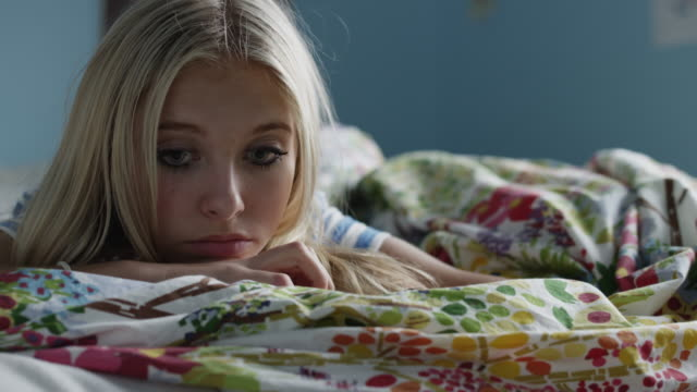 Close up of serious teenage girl laying on bed / Sandy, Utah, United States