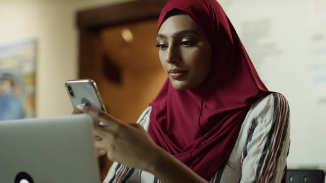 vídeos y material grabado en eventos de stock de close up of serious woman wearing hijab texting on cell phone then typing on laptop / cedar hills, utah, united states - asian and indian ethnicities