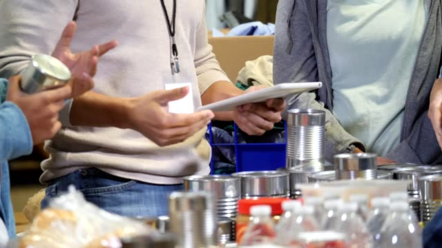 vídeos y material grabado en eventos de stock de cerca de varios voluntarios de pie alrededor de una mesa de suministros para empacar para la recolección de alimentos - caridad y auxilio