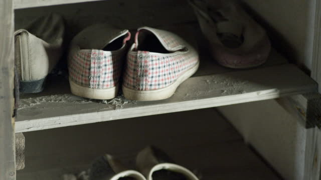 Close up of shoes and a child's tricycle inside a derelict building on abandoned Hashima Island