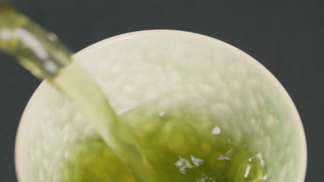 close up of single green cup filled with green tea - pour spout stock videos & royalty-free footage
