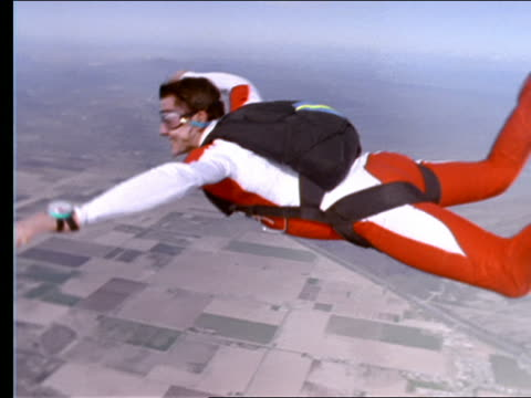 close up of skydiver spinning + flipping in air over farmland