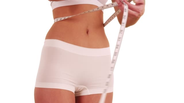 close up of slim young woman measuring waistline in studio with copy space - navel stock videos & royalty-free footage