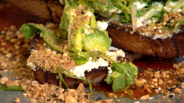 close up of smashed avocado feta dukkah greens puree on toast - feta stock videos & royalty-free footage