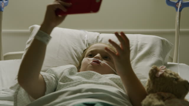 close up of smiling girl laying in hospital bed posing for cell phone selfie / salt lake city, utah, united states - telekommunikationsgerät stock-videos und b-roll-filmmaterial