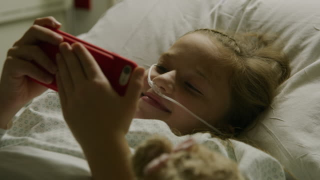 Close up of smiling girl laying in hospital bed video chatting on cell phone / Salt Lake City, Utah, United States
