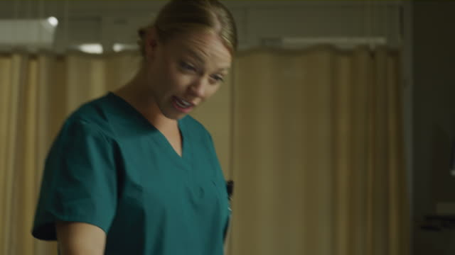 close up of smiling nurse arriving and talking to girl laying in hospital bed / salt lake city, utah, united states - moving toward stock videos & royalty-free footage