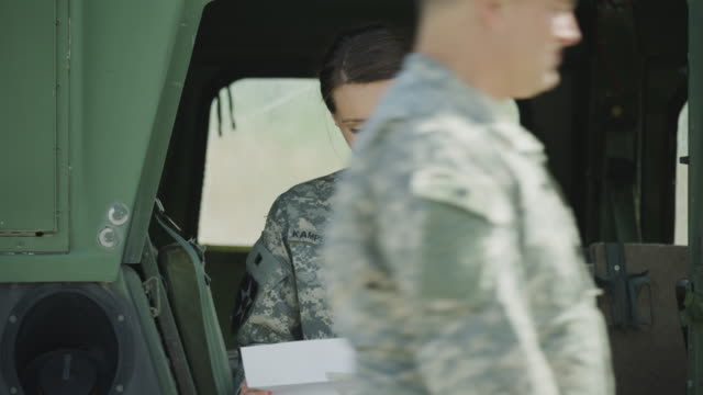 Close up of soldier standing near military vehicle reading paperwork / Lehi, Utah, United States