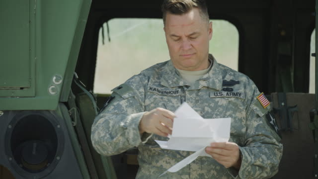 close up of soldier standing near military vehicle reading paperwork / lehi, utah, united states - lehi stock videos & royalty-free footage