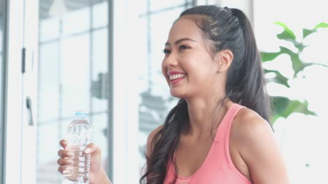 stockvideo's en b-roll-footage met sluit omhoog van sporty aziatische vrouw drinkwater na het uitoefenen thuis, 4k resolutie, slow motion - videoportret