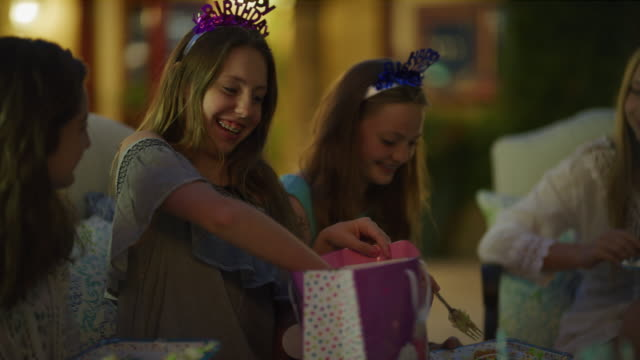 vídeos de stock e filmes b-roll de close up of surprised girl opening birthday gift from friend at party / cedar hills, utah, united states - 12 13 anos