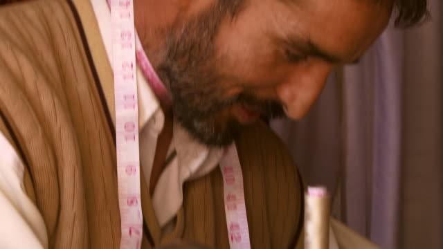 vídeos de stock, filmes e b-roll de close up of tailor hemming  - ponto de costura