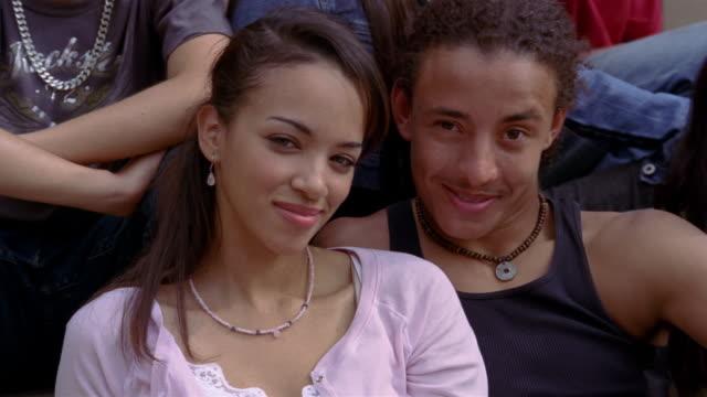 Close up of teenage couple smiling at camera