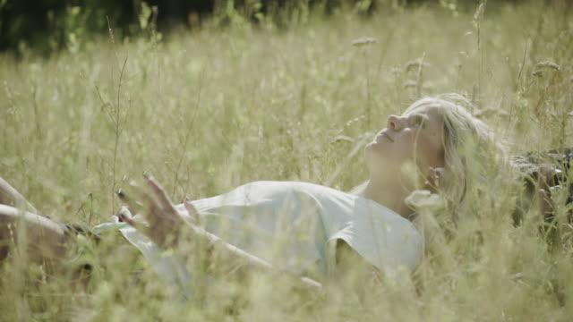 close up of teenage girl laying in grass listening to wireless earbuds / tibble fork, utah, united states - auf dem rücken liegen stock-videos und b-roll-filmmaterial