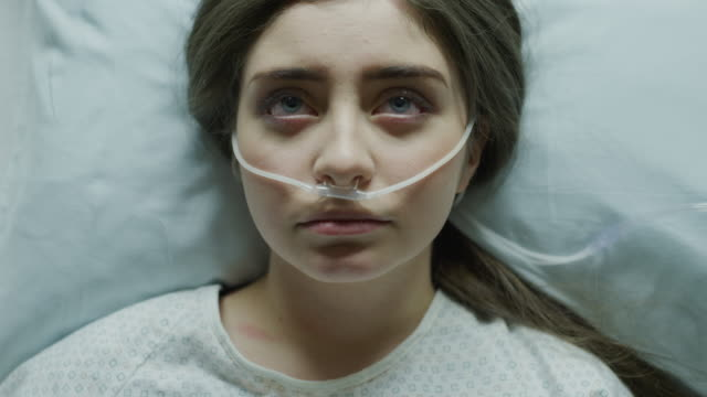 close up of teenage girl laying in hospital bed with breathing tubes in nose / salt lake city, utah, united states - kopfkissen stock-videos und b-roll-filmmaterial