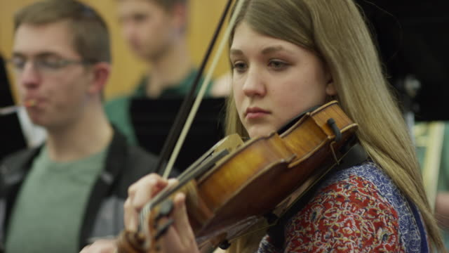 Close up of teenage girl playing violin in orchestra practice / American Fork, Utah, United States