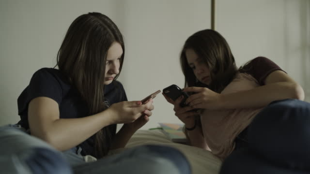 close up of teenage girls laying on bed using social media on cell phones / cedar hills, utah, united states - dreiviertelansicht stock-videos und b-roll-filmmaterial