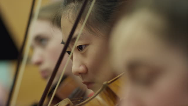 close up of teenage girls playing violins in orchestra practice / american fork, utah, united states - rehearsal stock videos & royalty-free footage