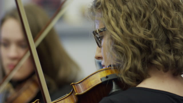 Close up of teenage girls playing violins in orchestra practice / American Fork, Utah, United States
