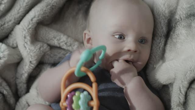 close up of teething baby boy chewing toy / cedar hills, utah, united states - endast en pojkbaby bildbanksvideor och videomaterial från bakom kulisserna