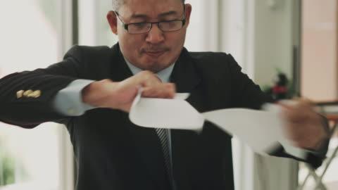 タイのクローズ アップ マネージャー男顔は事務所会議で否定的な感情との失望彼のジュニア チームのドキュメントを引き裂く - paperwork点の映像素材/bロール